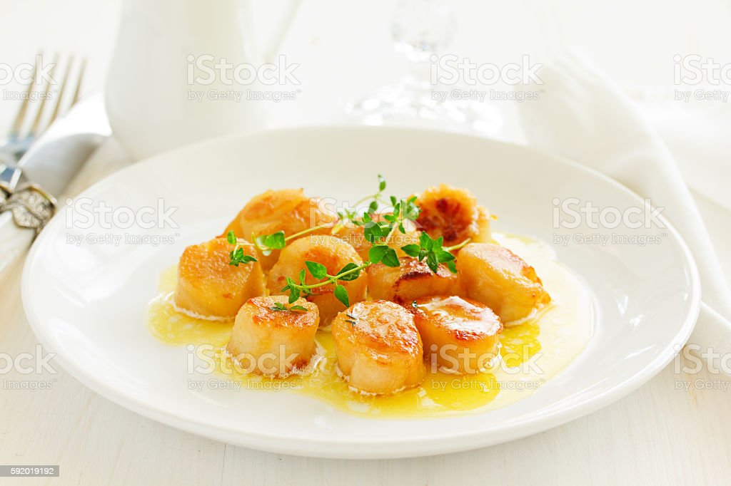 Scallops fried in cream sauce with herbs. stock photo