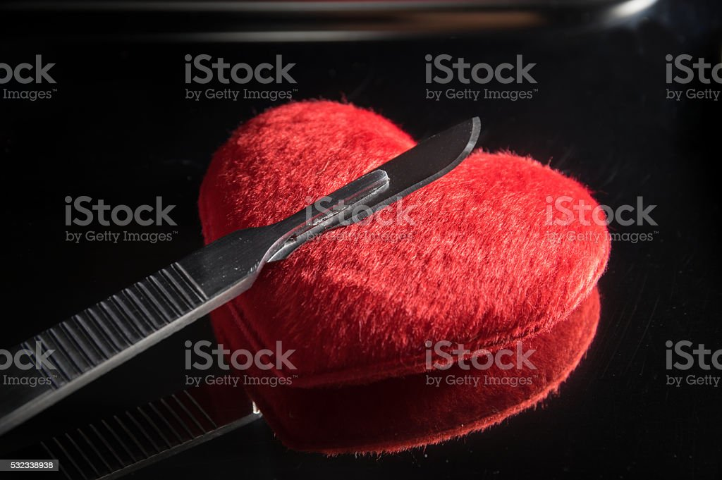 Scalpel on red heart,medical background. stock photo