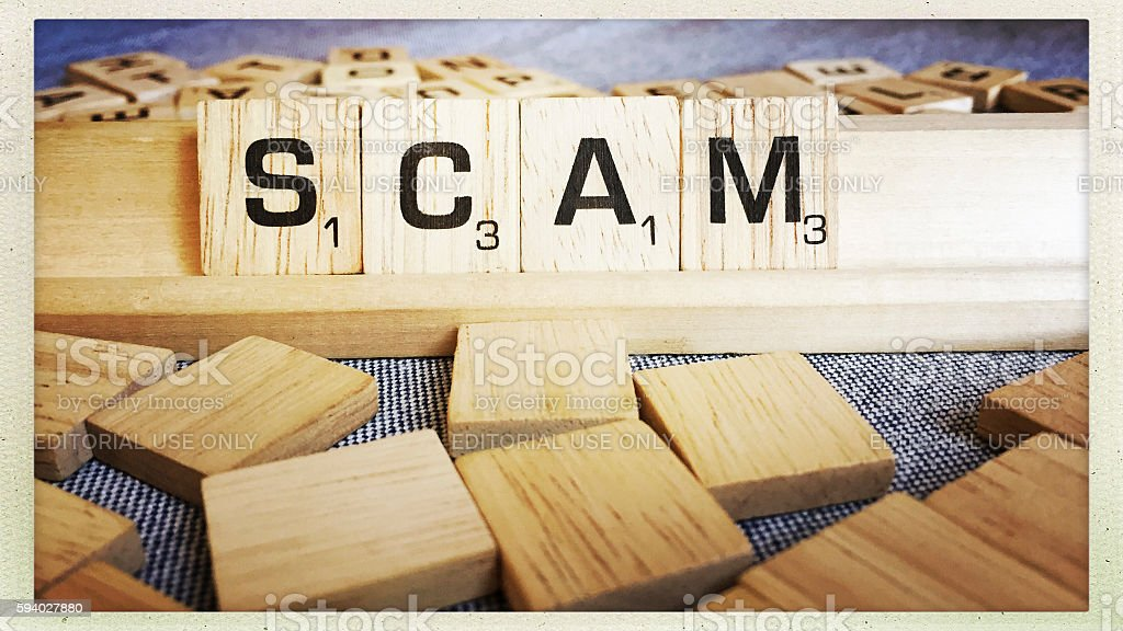 Scam Spelled with Scrabble Tiles Letters stock photo
