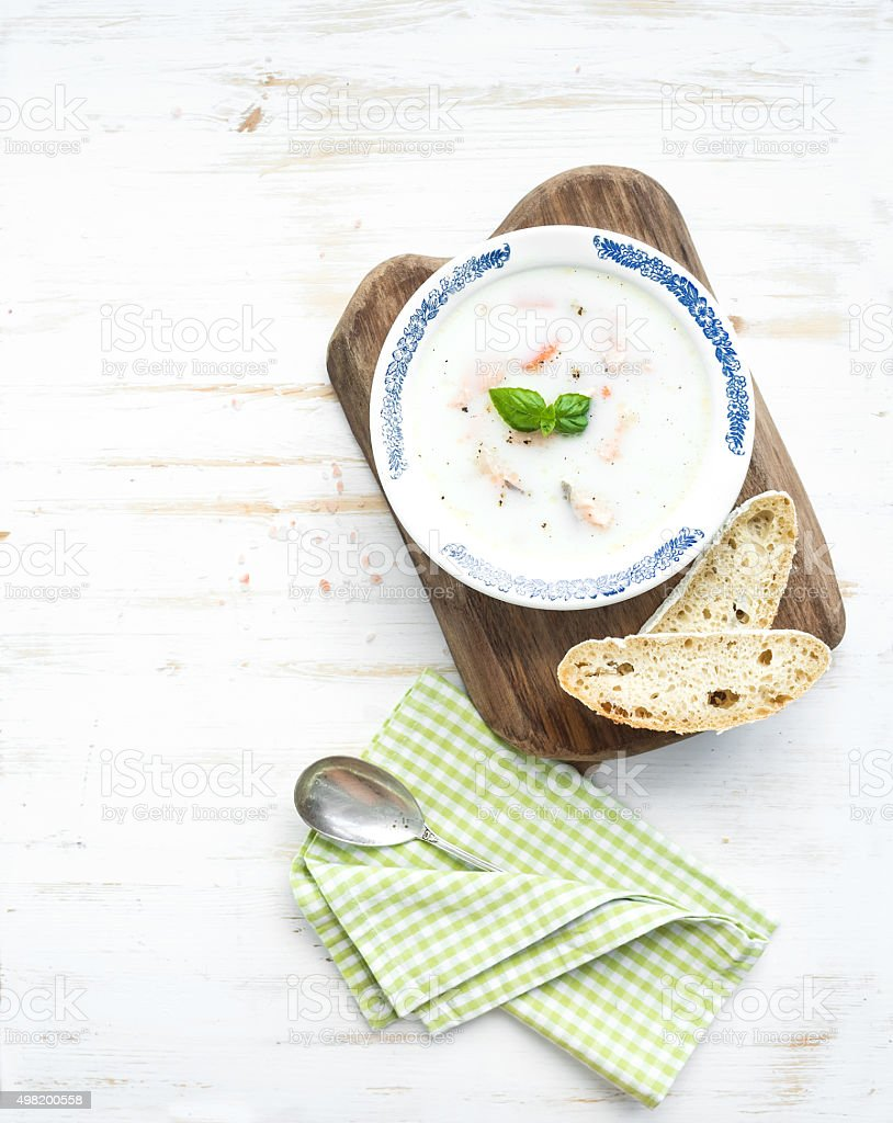 Scandinavian salmon soup with cream, fresh basil and bread in stock photo