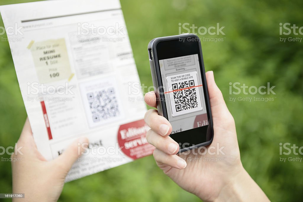 Scanning advertising with QR code on mobile phone stock photo