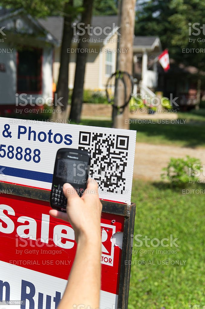 Scanning QR Code on For Sale Sign stock photo