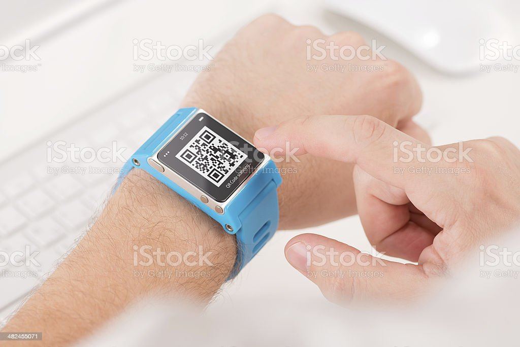 Scanning quick response code with smart watch stock photo