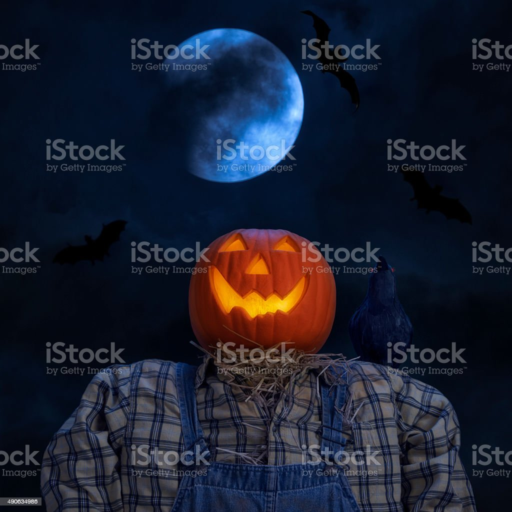 Scarecrow, crow and bats with cloudy blue full moon stock photo