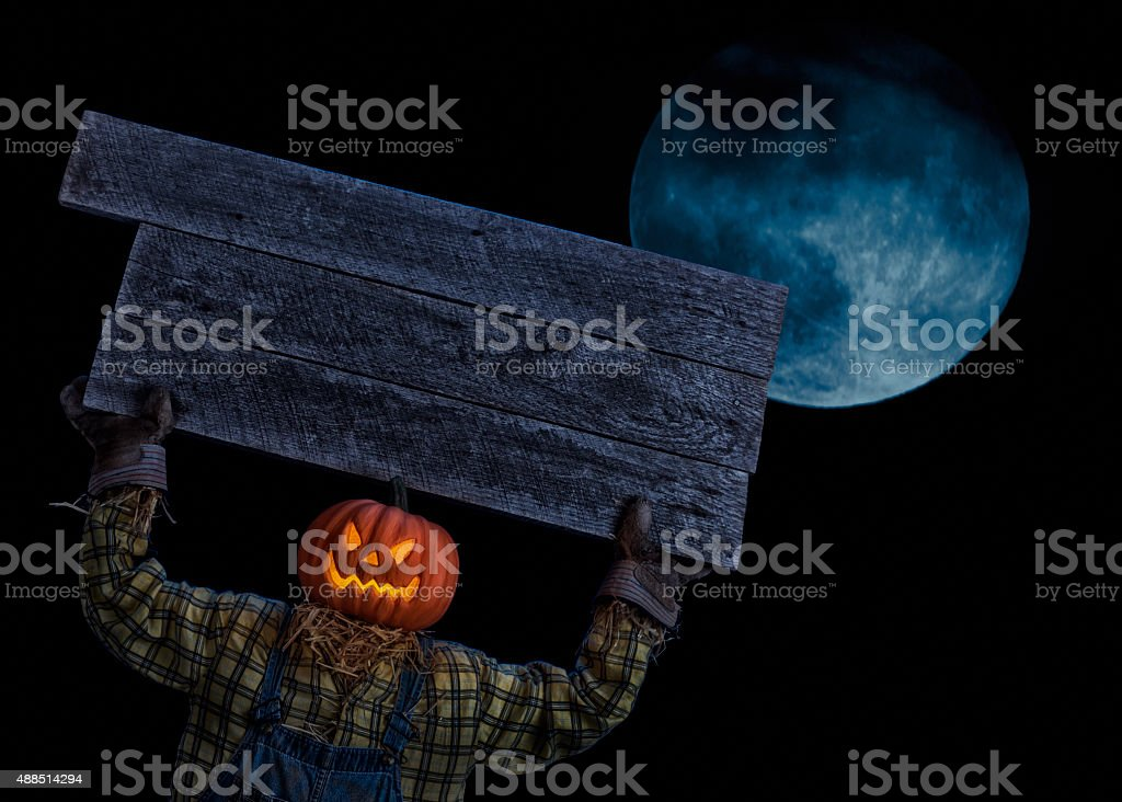 Scarecrow holding a sign overhead with a hazy full moon stock photo