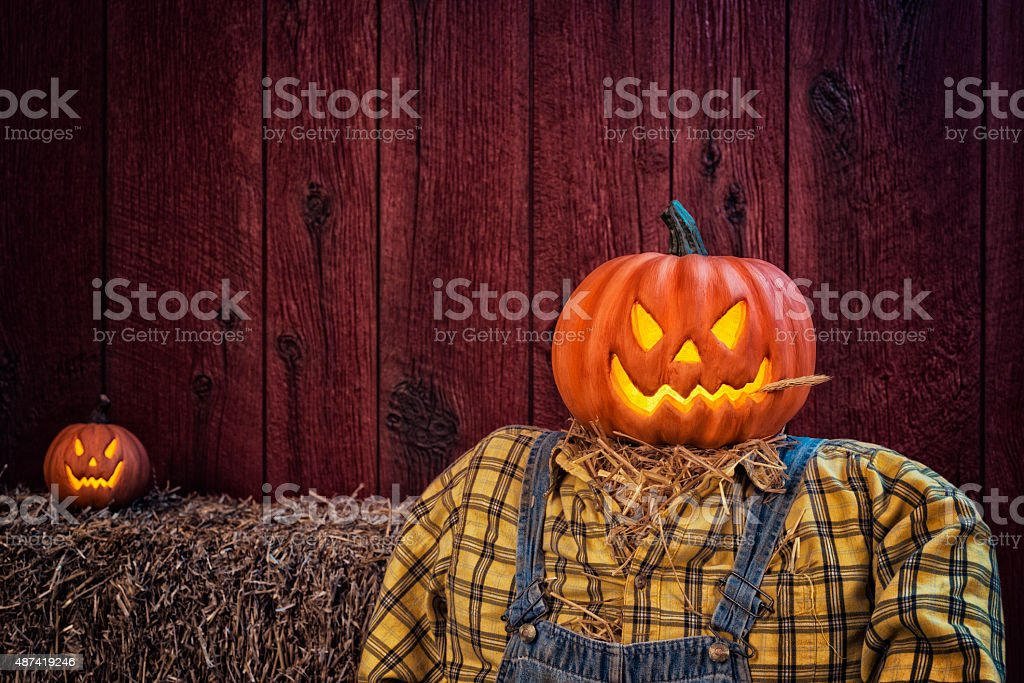 Scarecrow sitting in front of a red barn stock photo