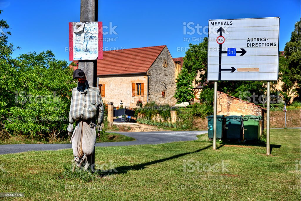 Scarecrow tied to wooden telegraph pole in French village stock photo