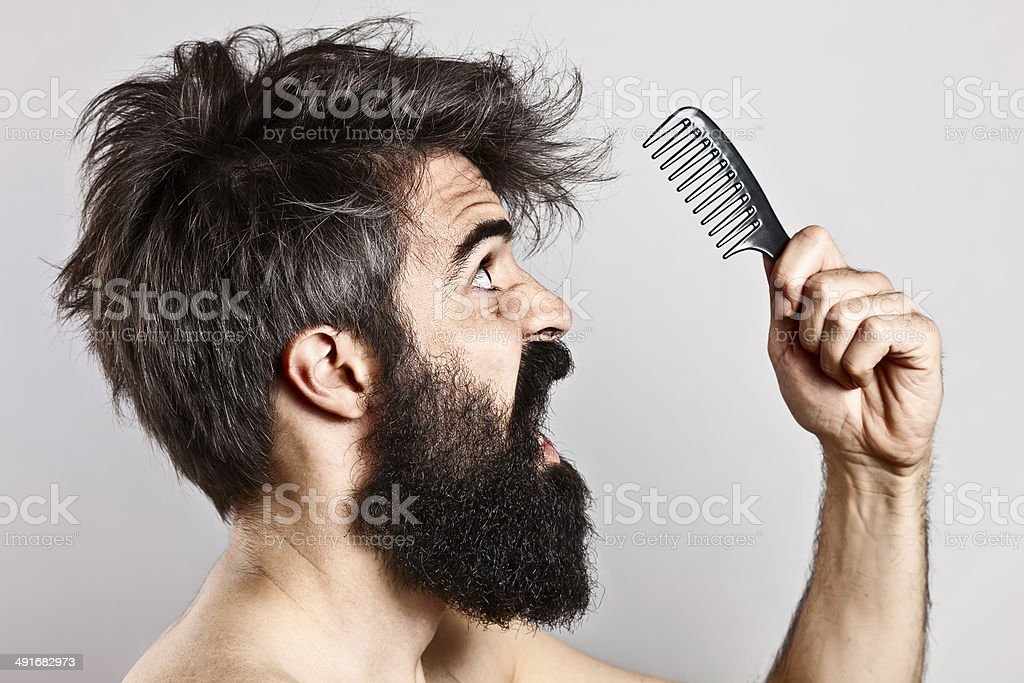 Scared bearded man with messy hair staring at a comb stock photo