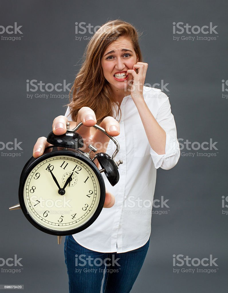 scared beautiful woman showing stressful alarm clock for worrying deadlines stock photo
