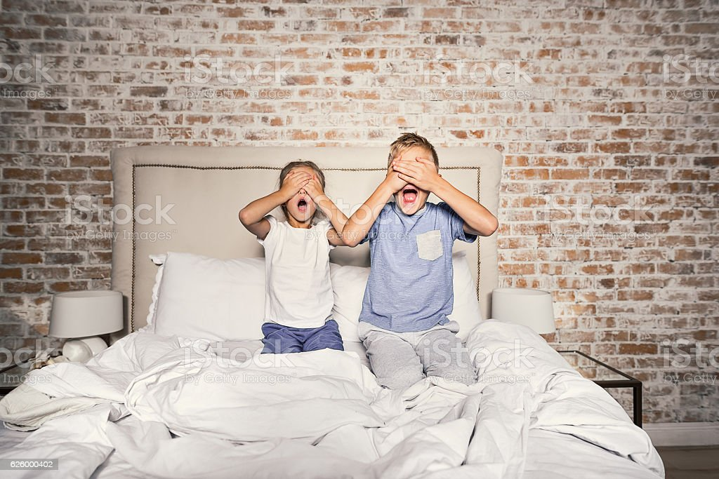 Scared brother and sister in bedroom stock photo