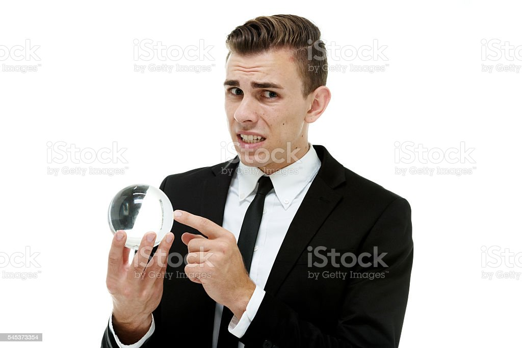 Scared businessman holding crystal ball stock photo