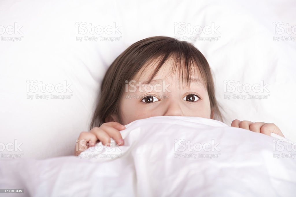 Scared cute girl laying under duvet stock photo
