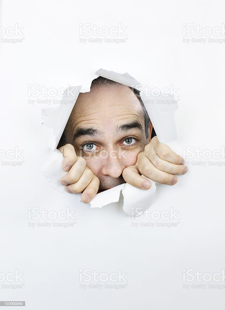 Scared face looking through hole in paper royalty-free stock photo