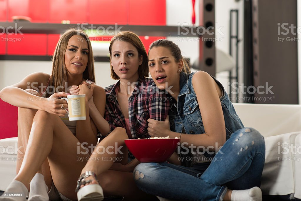 Scared female friends watching a movie together at home. stock photo