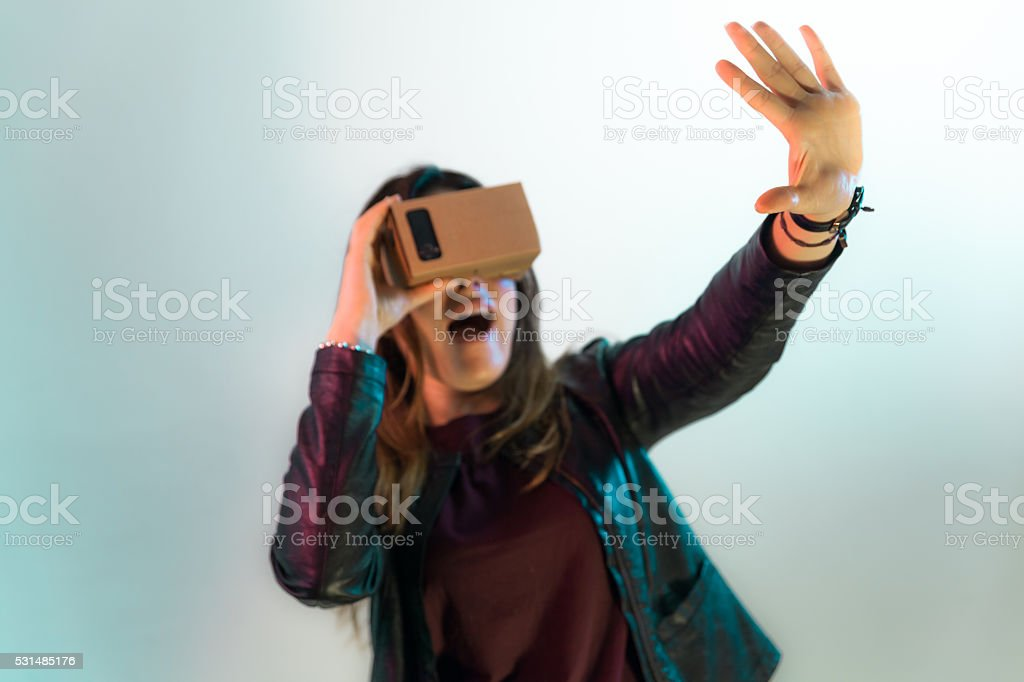 Scared girl tries to touch something in a VR world stock photo