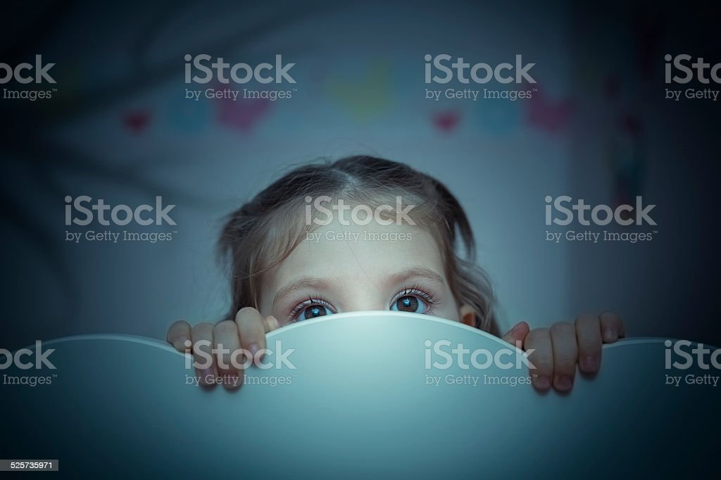 scared little girl in her bed stock photo