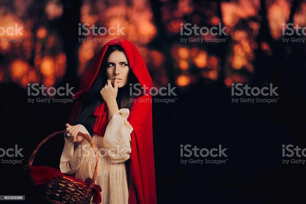 Scared Little Red Riding Hood Hiding in the Forest stock photo
