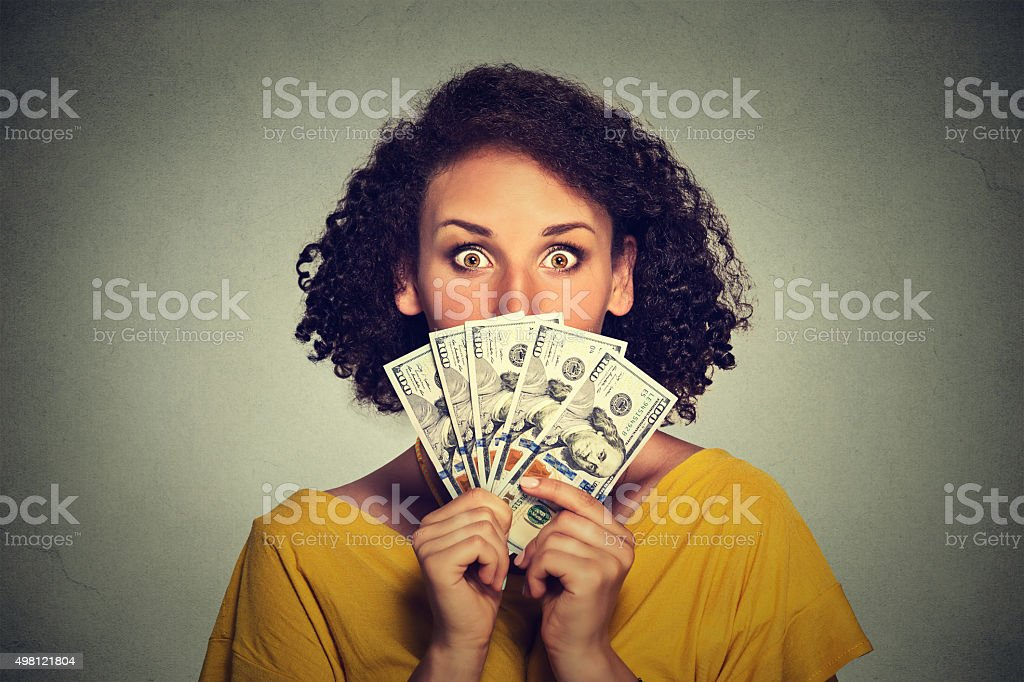 Scared looking woman picking through dollar banknotes stock photo