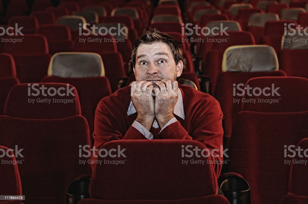 Scared Man Sitting in Movie Theatre Alone royalty-free stock photo