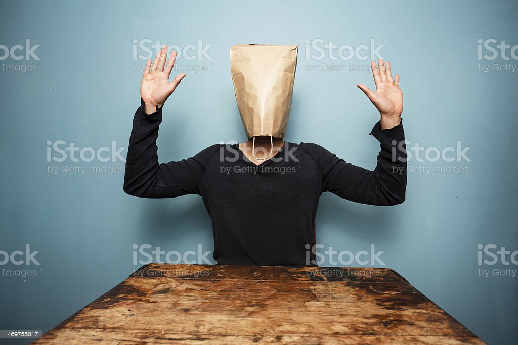 scared man with bag over head stock photo