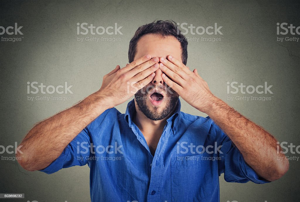 scared man with wide open mouth covering eyes with hands stock photo