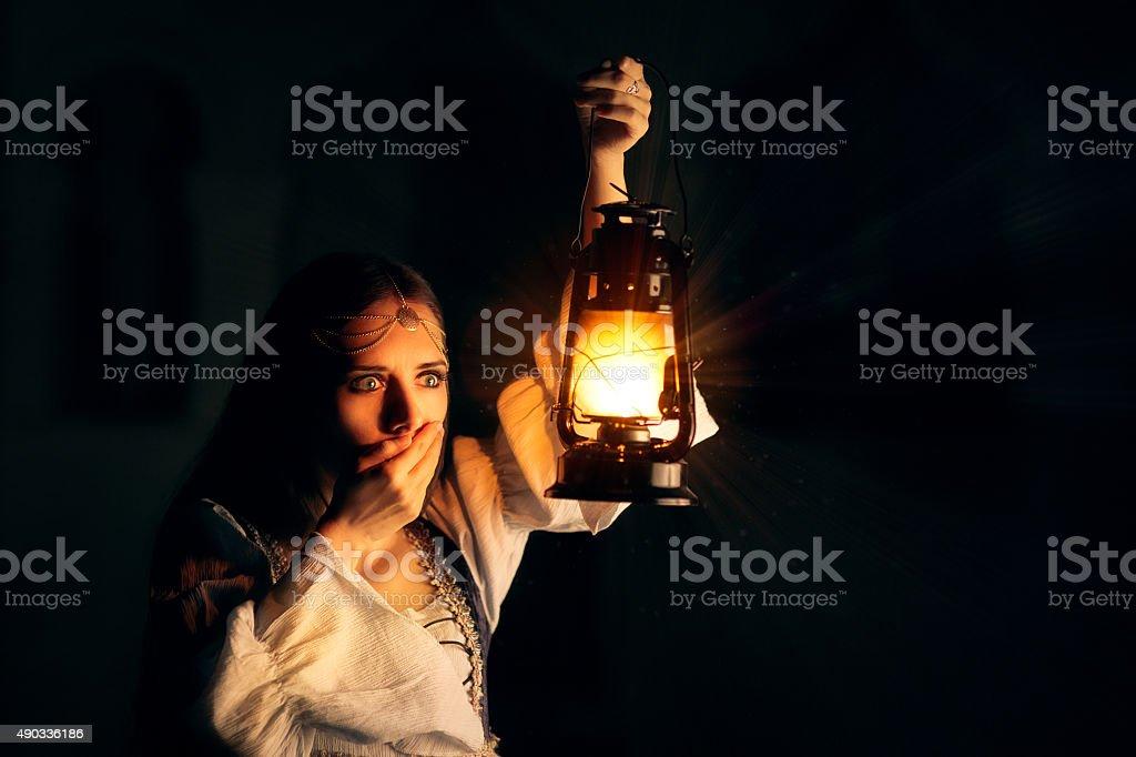 Scared Medieval Princess Holding Lantern stock photo