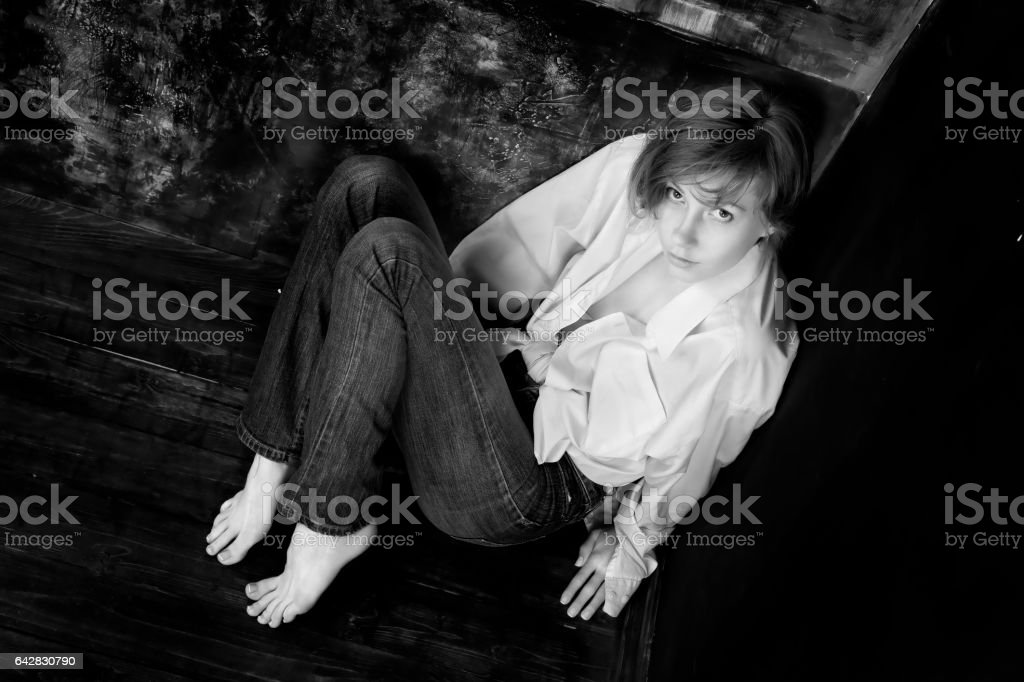 Scared or alarming woman in casual sitting in the corner stock photo
