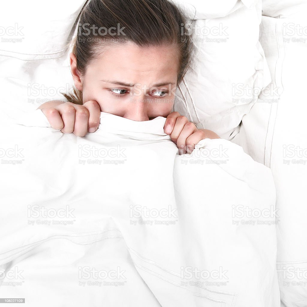 Scared woman hiding under white bed covers pulled up to nose royalty-free stock photo