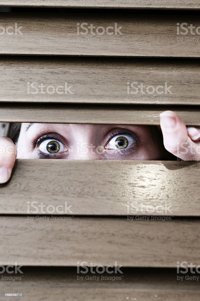 Scared woman peeps through blinds, vulnerable and nervous stock photo