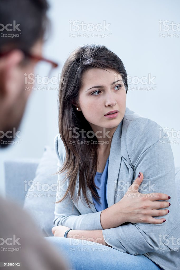 Scared woman receiving psychotherapy stock photo
