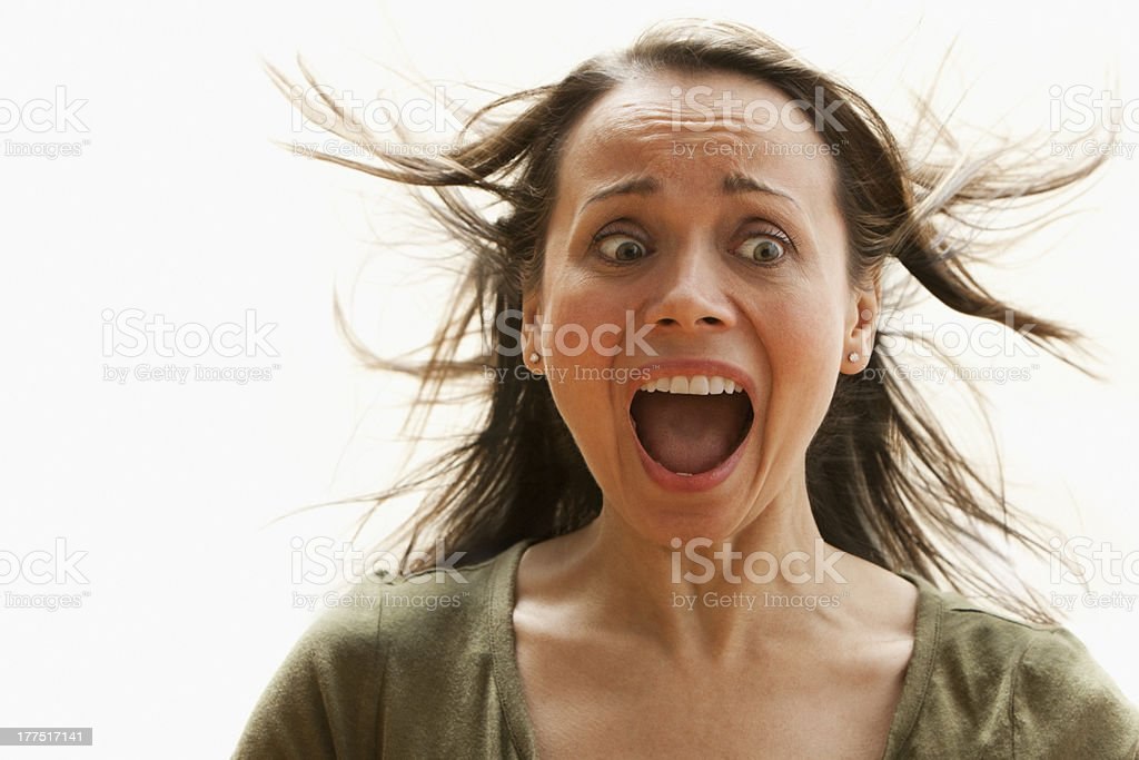 Scared woman screaming with hair blowing stock photo