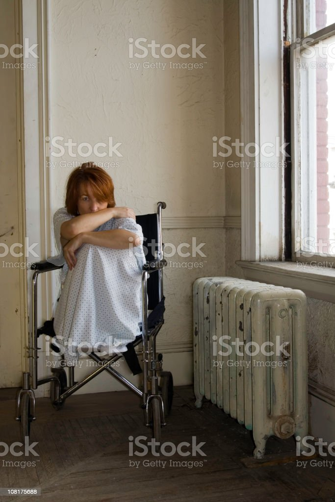 Scared Woman Sitting in Hospital Wheelchair by Window stock photo