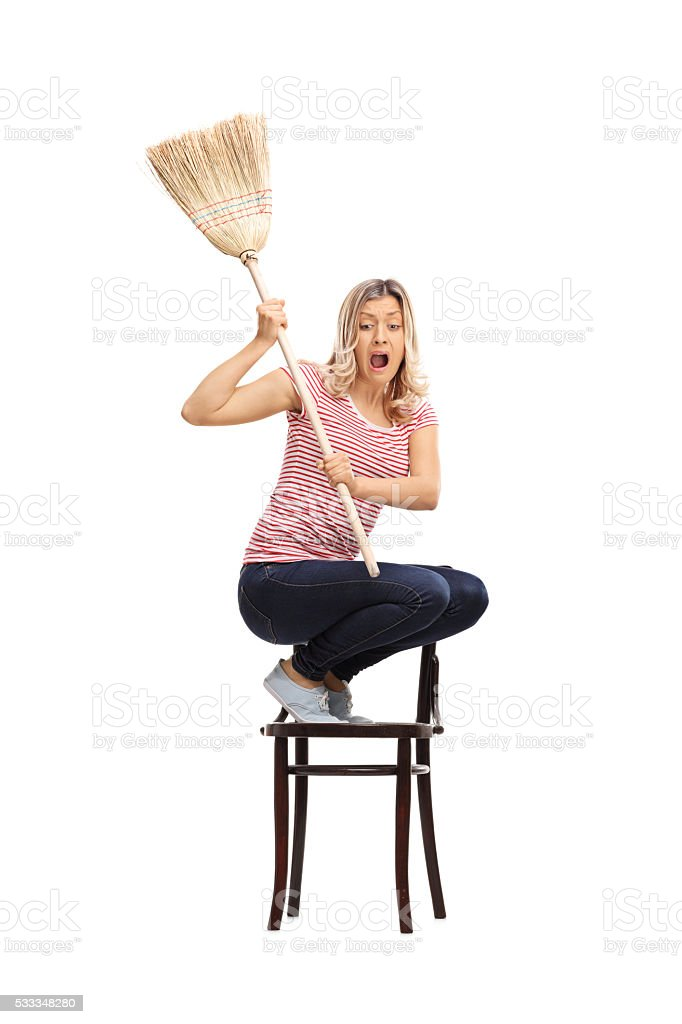 Scared woman swinging with a broom stock photo