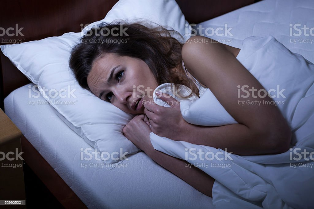Scared woman trying to sleep stock photo