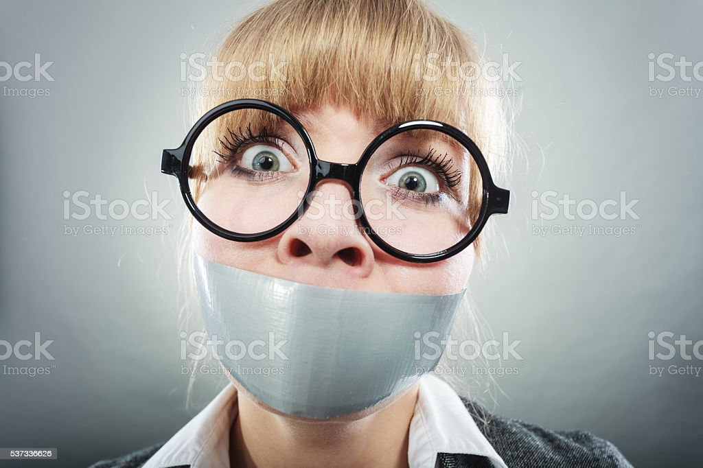 Scared woman with mouth taped shut. Censorship. stock photo