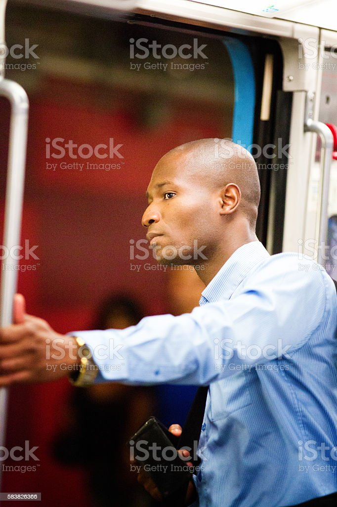 Scared worried black man looks out of train at disturbance stock photo