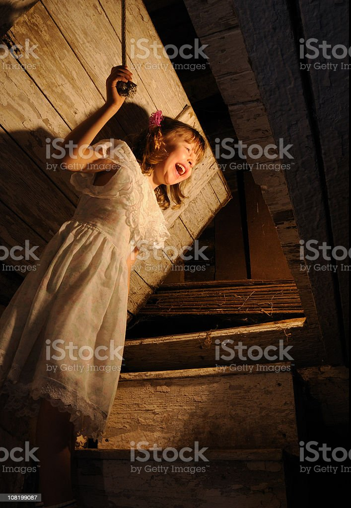 Scared Young Girl Looking in Attic stock photo