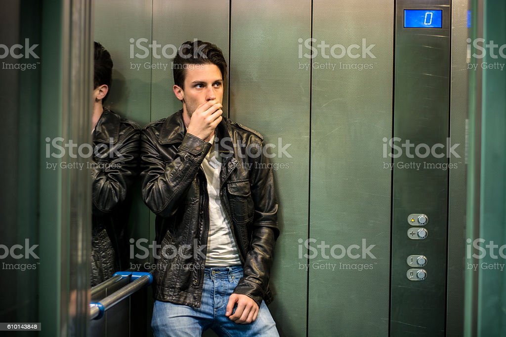 Scared young man desperate in stuck elevator stock photo