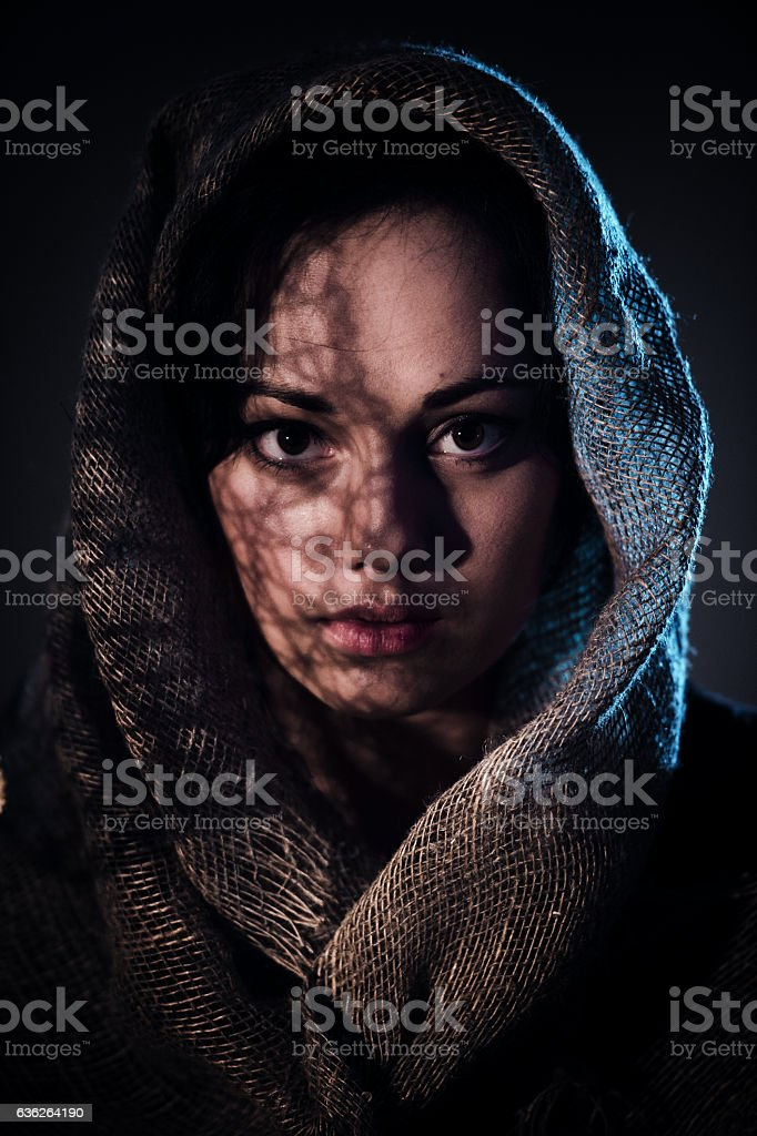 Scared young woman covering face with afghan scarf stock photo