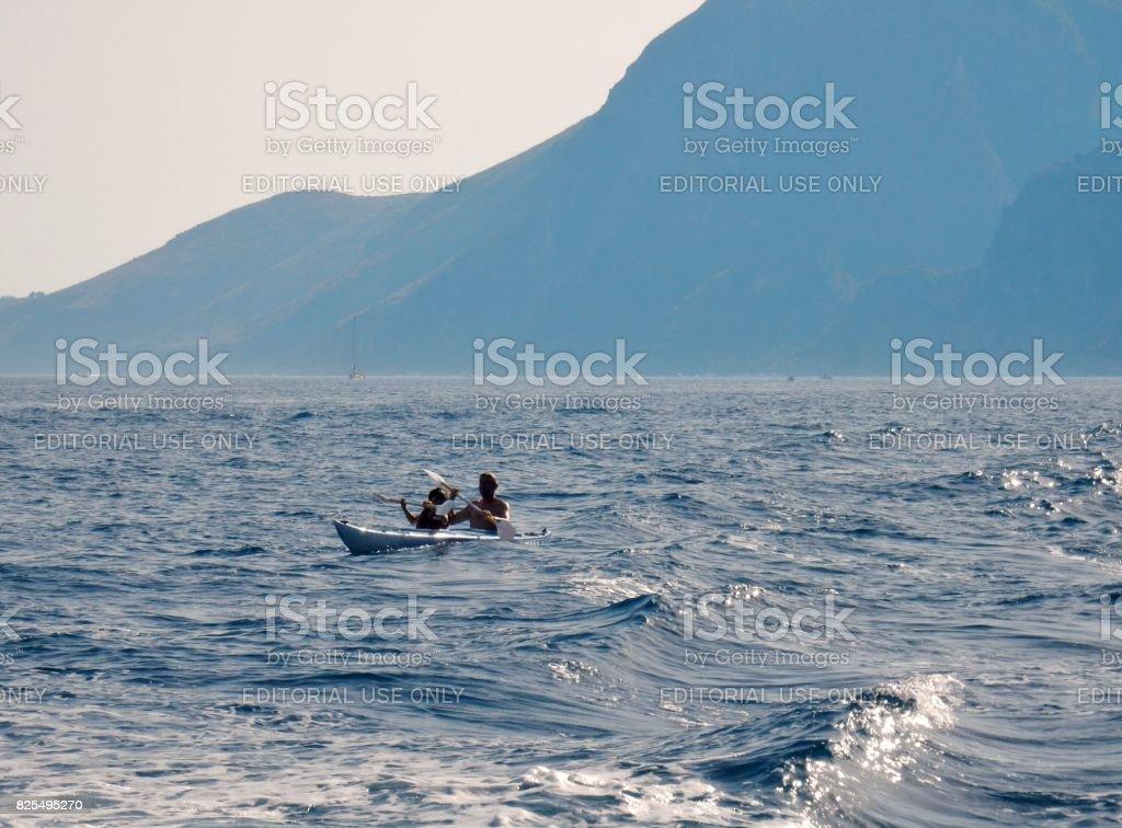 Scario - Canoa in balia delle onde stock photo
