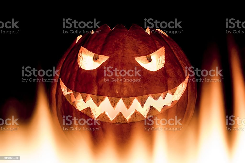 Scary carved halloween pumpkin in hot burning hell fire flames stock photo