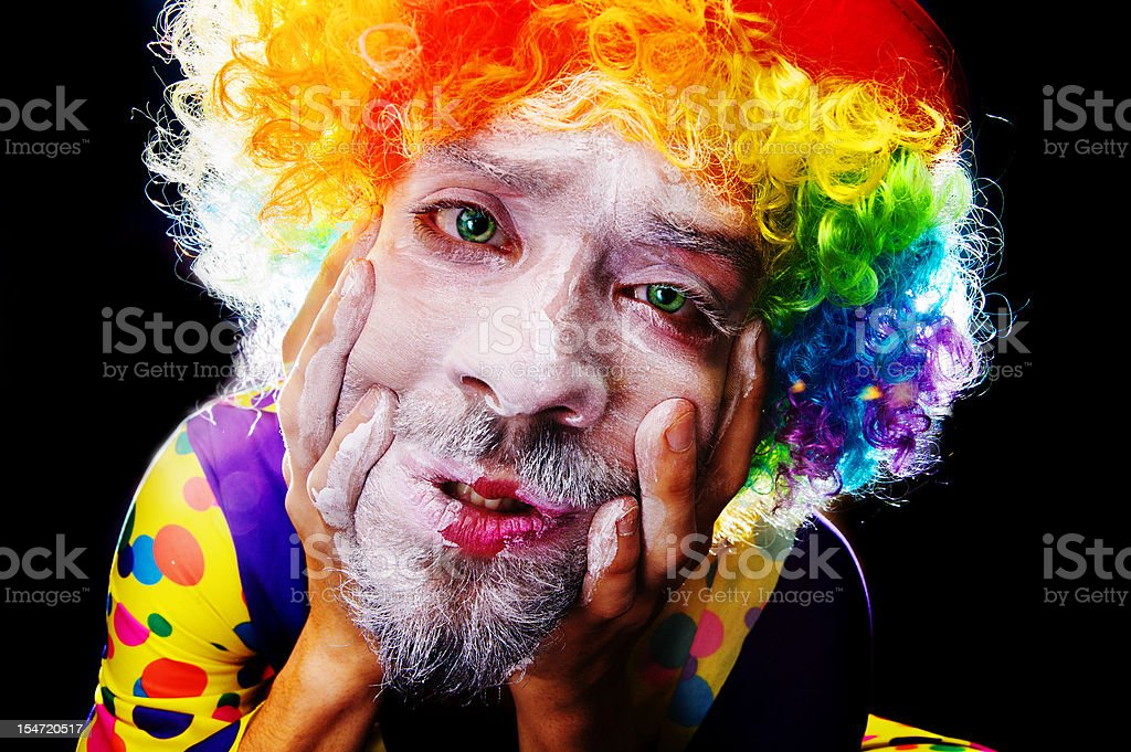 Scary Clown Man Applying Face Paint stock photo