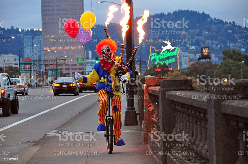 Scary Clown Riding a Unicycle Playing Flaming Bagpipes in Portland stock photo