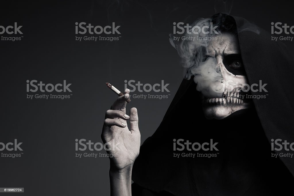 Scary Death Makes Cloud Of Smoke. The Concept 'Smoking Kills'. stock photo