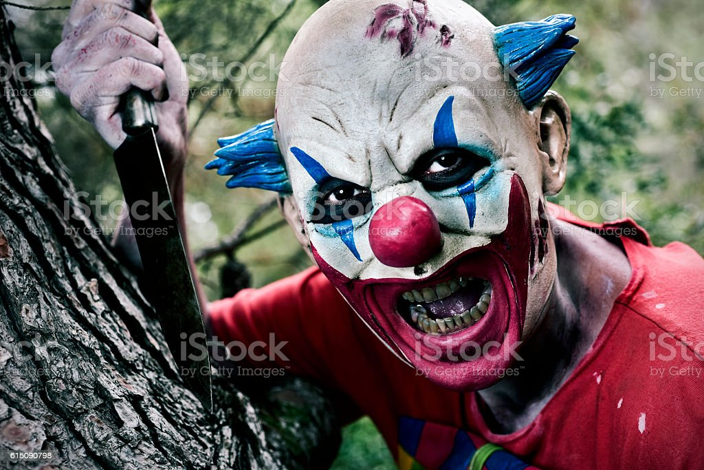 scary evil clown with a knife stock photo