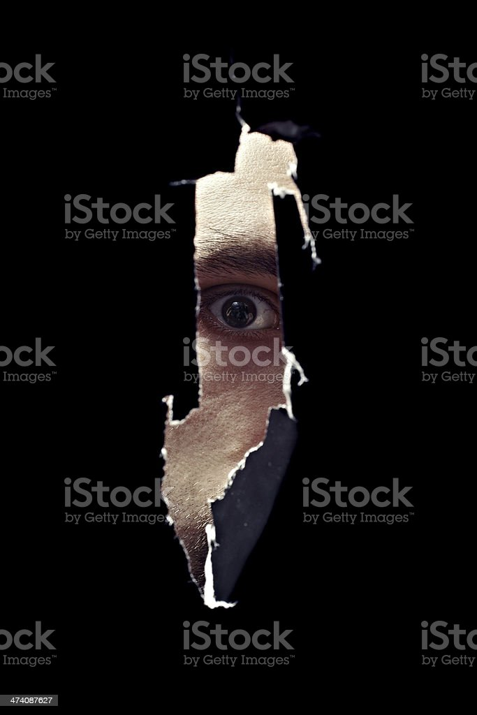 Scary eye of a man spying through a hole stock photo