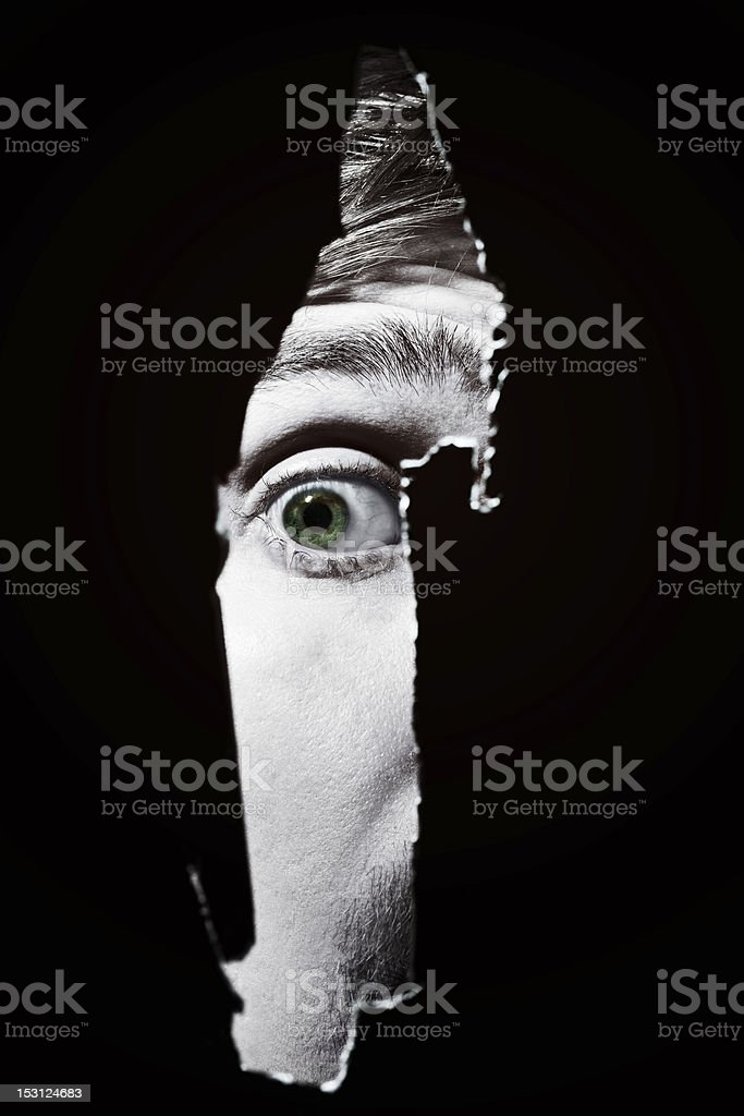 Scary eyes of man spying through  hole in the wall stock photo