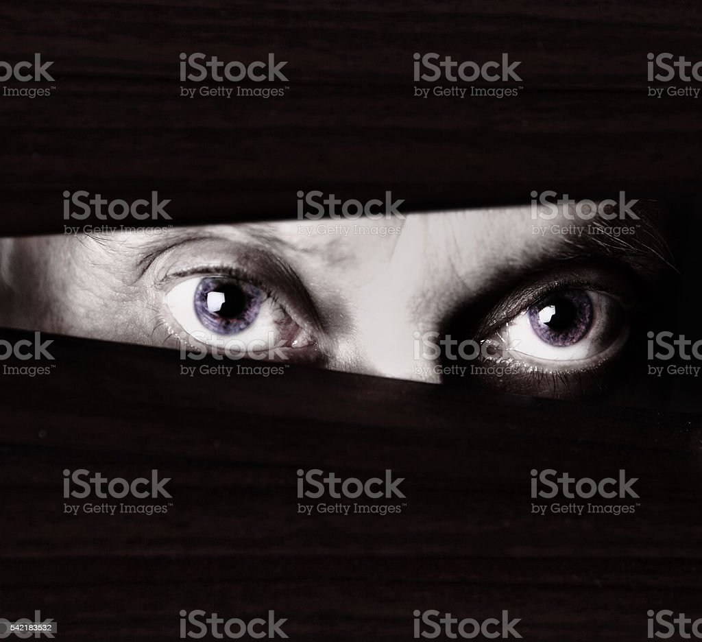 Scary eyes staring through blinds in monochrome close up stock photo