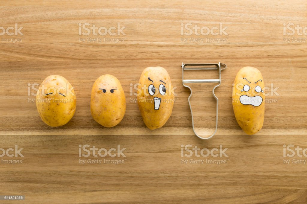 Scary face potatoes and peeler on wooden cutting board stock photo