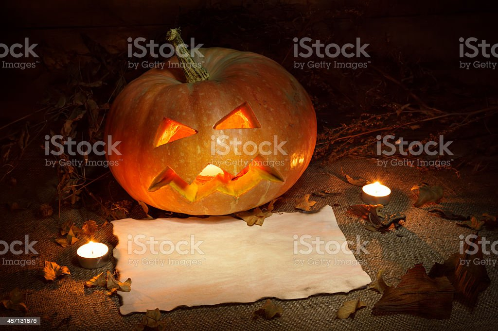 Scary Halloween pumpkin and old burned paper stock photo